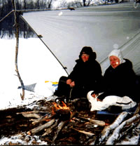 Gail Bosio and Mary Powell enjoy a small fire under a tarp shelter